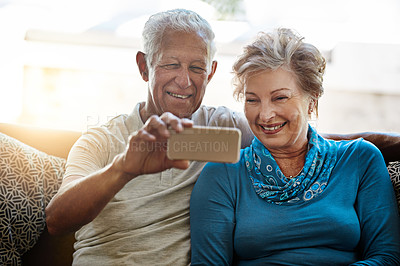 Buy stock photo Shot of a happy senior couple taking a selfie together on the sofa at home