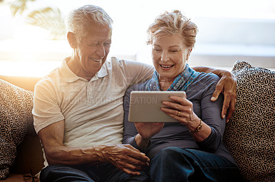 Buy stock photo Shot of a happy senior couple using a digital tablet together on the sofa at home