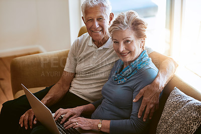Buy stock photo Portrait of a happy senior couple using a laptop together on the sofa at home