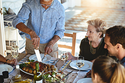 Buy stock photo Shot of a mature man carving a roast while enjoying lunch with his family outside