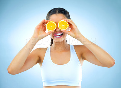 Buy stock photo Studio shot of a healthy young woman holding up oranges in front of her eyes against a blue background