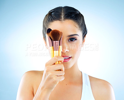 Buy stock photo Cropped portrait of a beautiful young woman holding up makeup brushes against a blue background