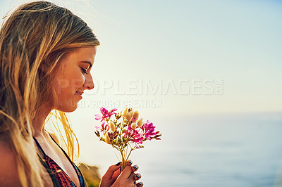 Buy stock photo Shot of a happy young woman holding a bunch of flowers while standing outside