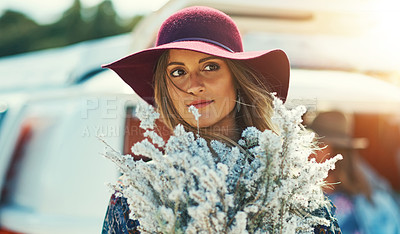 Buy stock photo Shot of a young woman standing outside with a bouquet of wildflowers