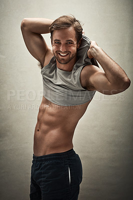 Buy stock photo Studio shot of a handsome and shirtless young man removing his vest to show off his six pack