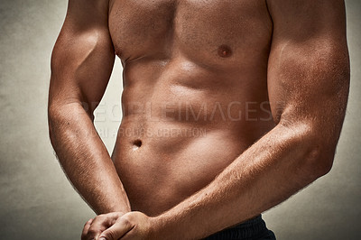 Buy stock photo Cropped studio shot of a muscular man flexing his muscles