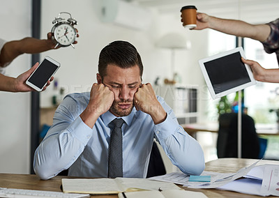 Buy stock photo Shot of a stressed out businessman surrounded by demanding colleagues in an office