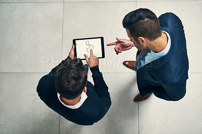 Buy stock photo High angle shot of two businessmen working together on a digital tablet in an office