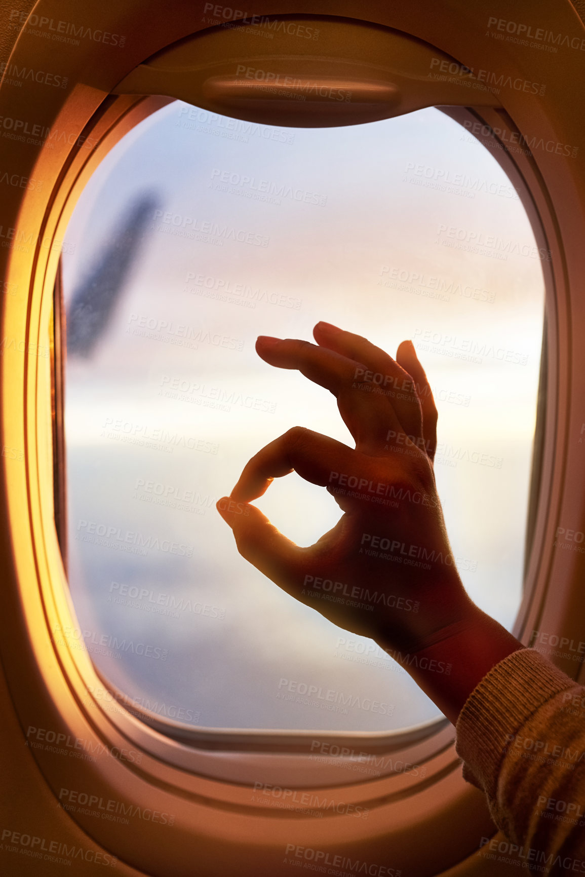 Buy stock photo Shot of a passenger making an okay sign while looking through the window of an airplane