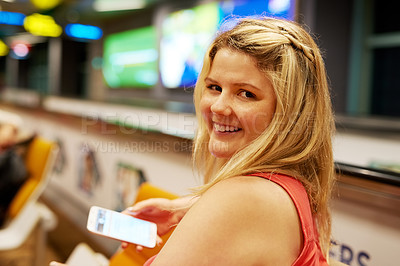 Buy stock photo Portrait of a young woman using a cellphone while sitting in an airport departure lounge