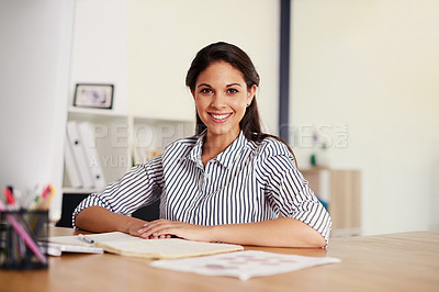 Buy stock photo Portrait of a confident young businesswoman sitting at her desk in an office