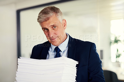 Buy stock photo Portrait of a mature businessman holding a pile of paperwork in an office