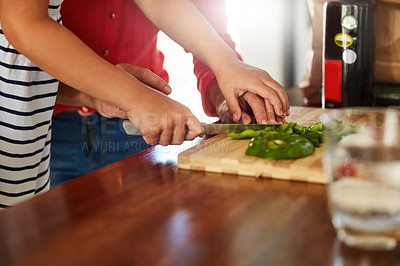 Buy stock photo Shot of an unidentifiable mother helping her little girl chop vegetables in the kitchen