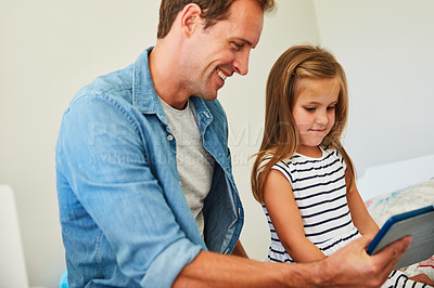 Buy stock photo Shot of a father and his young daughter sitting together in the living room at home using a digital tablet