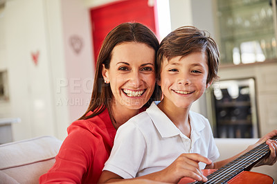 Buy stock photo Portrait of a mother and her young son sitting together in the living room at home playing guitar