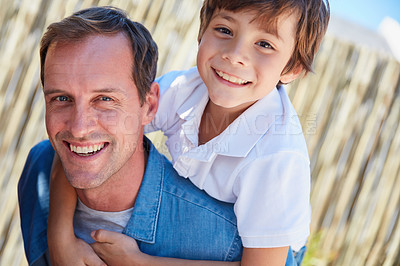 Buy stock photo Portrait of smiling father giving his young son a piggyback outside in their yard on a sunny day
