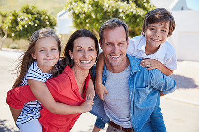 Buy stock photo Portrait of smiling parents giving their young son and daughter a piggyback outside in their yard on a sunny day