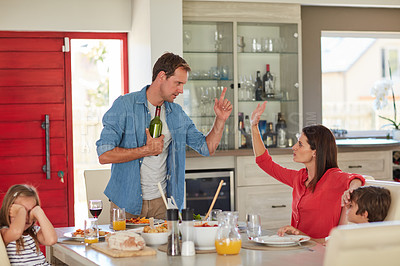 Buy stock photo Shot of a drunk man and his wife arguing in front of their children during lunch
