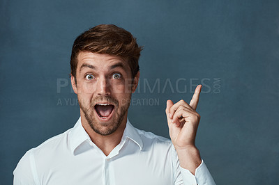 Buy stock photo Studio portrait of a handsome young man pointing excitedly to copyspace against a dark background