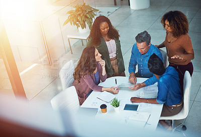 Buy stock photo Shot of a group of designers gathering around a man using a tablet in a meeting