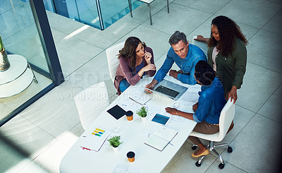 Buy stock photo Shot of a group of designers gathering around a man using a laptop in a meeting