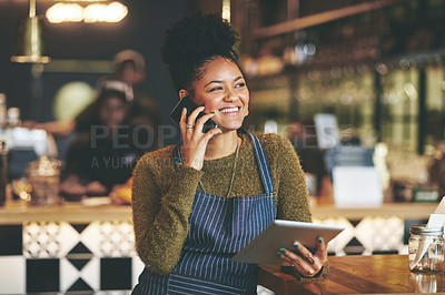 Buy stock photo Shot of a young woman using a phone and digital tablet while working at a coffee shop
