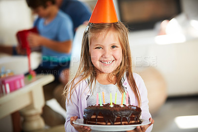 Buy stock photo Portrait of a happy little girl holding a birthday cake with her family in the background