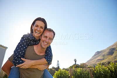 Buy stock photo Cropped shot of a man giving his wife a piggyback ride