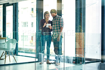 Buy stock photo Full length shot of two young coworkers talking while looking at a digital tablet