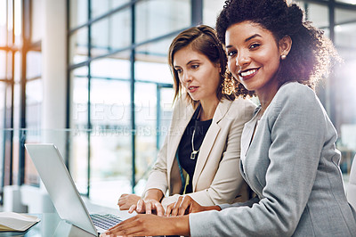 Buy stock photo Shot of two young businesswomen using a laptop together at work