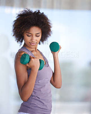 Buy stock photo Cropped shot of an attractive young woman working out with dumbbells