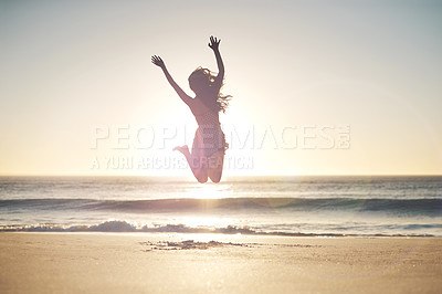 Buy stock photo Shot of a young woman jumping into mid air at the beach