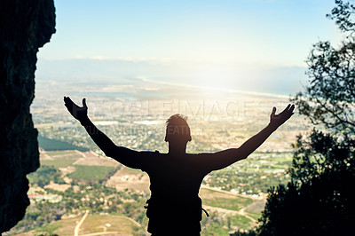 Buy stock photo Rearview shot of a young man standing at the top of a mountain with his arms outstretched