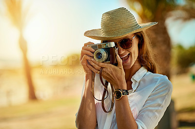 Buy stock photo Shot of an attractive young woman using a camera on a summer's day outdoors
