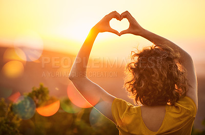 Buy stock photo Rearview shot of an unidentifiable woman making a heart shape with her hands over a sunset landscape