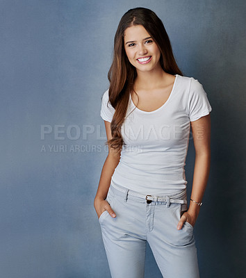 Buy stock photo Studio shot of an attractive young woman posing with her hands in her pockets