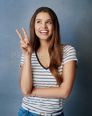 Buy stock photo Studio shot of an attractive young woman showing the peace sign against a gray background