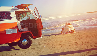 Buy stock photo Shot of a couple admiring the view on the beach while out on a road trip