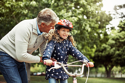 Buy stock photo Cropped shot of a grandfather teaching his little granddaughter how to ride a bicycle