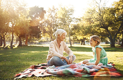 Buy stock photo Shot of a little girl and her grandmother having a picnic at the park