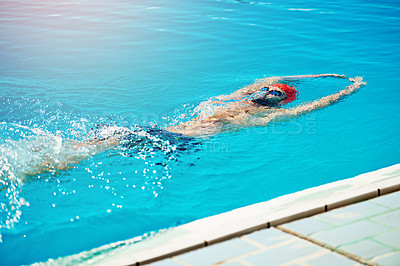 Buy stock photo Shot of a handsome young male swimmer doing backstroke in a swimming pool