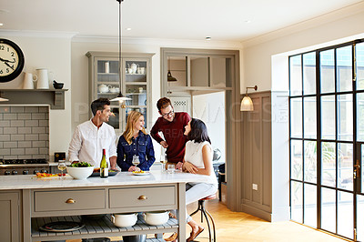 Buy stock photo Shot of two young couples having a chat while chilling in the kitchen