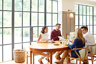 Buy stock photo Shot of two young couples sitting around the dining room table