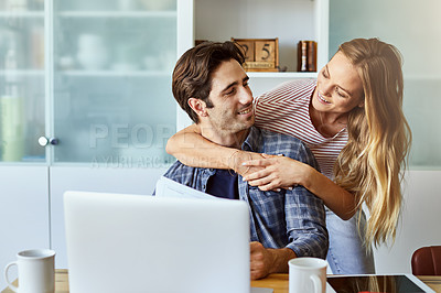 Buy stock photo Shot of a young woman hugging her husband while he works on his laptop at home
