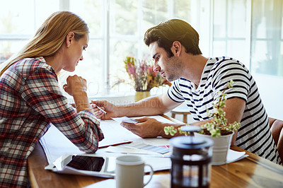 Buy stock photo Shot of an affectionate young couple looking over some paperwork at home