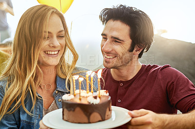 Buy stock photo Shot of an affectionate young couple celebrating a birthday with a chocolate cake