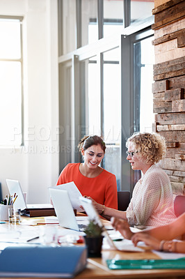 Buy stock photo Shot of two businesswoman looking over some paperwork in the office
