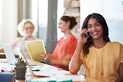 Buy stock photo Shot of an attractive young woman talking on the phone in her office