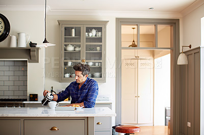 Buy stock photo Shot of a young man pouring coffee while having breakfast at home