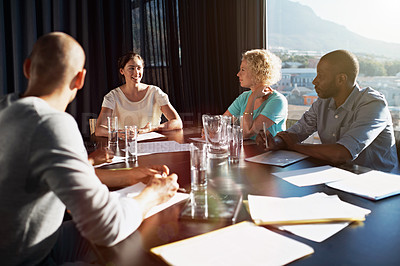 Buy stock photo Shot of four businesspeople sitting around a table in the boardroom